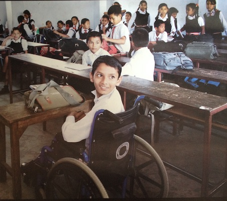 School student in a wheelchair sitting in class with other students